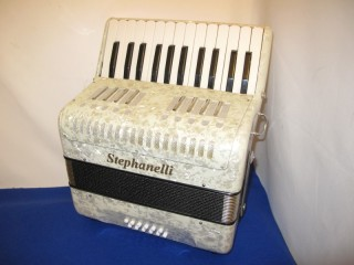 New white stephanelli accordion with 26 treble keys and 12 bass